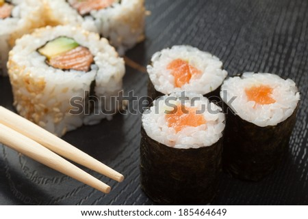 sushi rolls assortment on black plate and wooden chopsticks