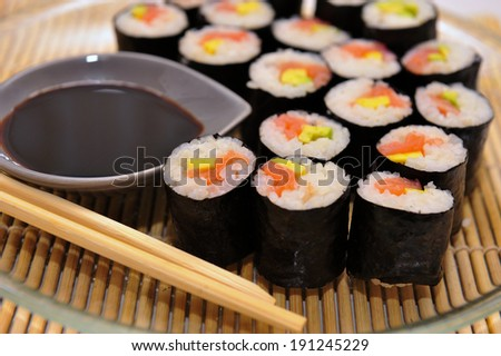Sushi rolls on a plate with chopsticks and soy sauce, side view