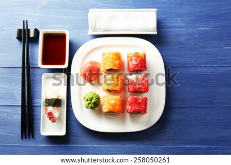 Sushi rolls on plate, soy sauce and chopsticks on color wooden background - stock photo