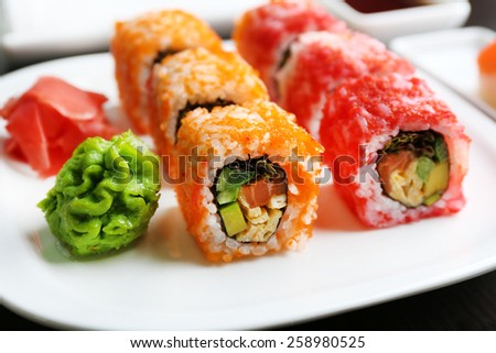 Sushi rolls on plate, soy sauce and chopsticks on wooden background - stock photo