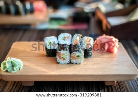 Sushi rolls served on a wooden plate in a restaurant. - stock photo