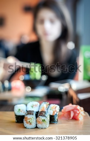 Sushi rolls served on a wooden plate in a restaurant with blurred woman on background, vertical composition. Very shallow DOF, focus is on the first row of rolls. - stock photo