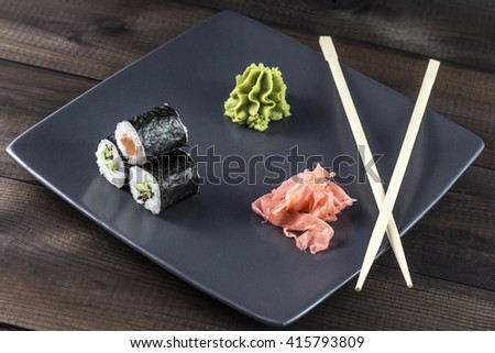 Sushi rolls set. Kappamaki and Sakemaki with pickled ginger and wasabi served on grey plate with sushi sticks. - stock photo
