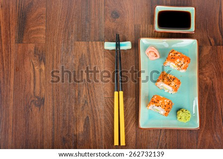 Sushi rolls with masago, served on turquoise plate with pickled ginger, soy sauce and chopsticks on wooden table. Sushi rolls on the wooden table. View from above. - stock photo