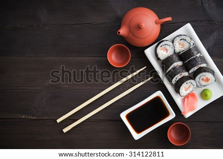 Sushi rolls with salmon and hot tea ceremony on black wooden table - stock photo