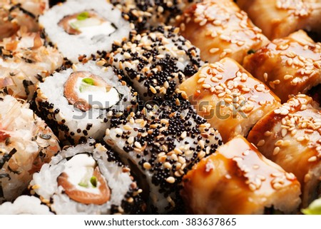 Sushi rolls with salmon, black caviar and sesame close-up macro shot - stock photo