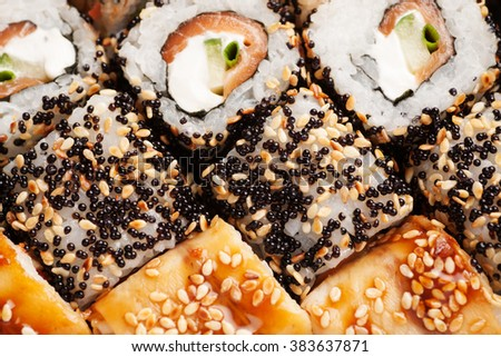 Sushi rolls with white rice, salmon, sesame and black caviar macro shot