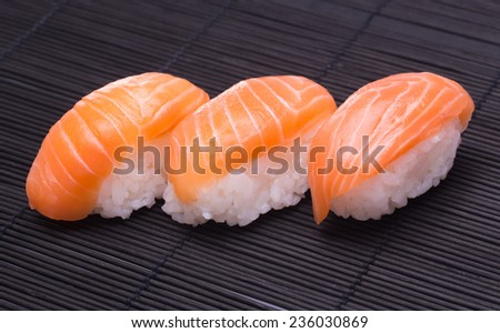 sushi salmon on wooden bamboo color black - stock photo