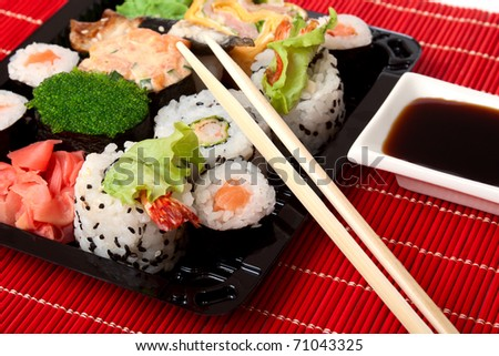 Sushi, sauce and wood chopstick on red bamboo napkin - stock photo