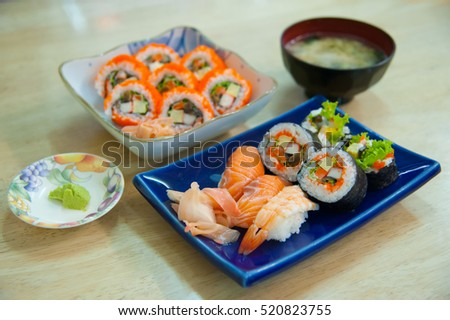 Sushi set and California Maki Japanese food with side dish on wooden table at home