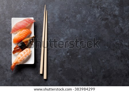 Sushi set and chopsticks on stone table. Top view with copy space - stock photo