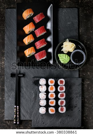 Sushi set nigiri and rolls served with chopsticks and soy sauce on black stone slate. Flat lay. - stock photo