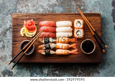 Sushi Set nigiri and sushi rolls served for two on wooden serving board block - stock photo