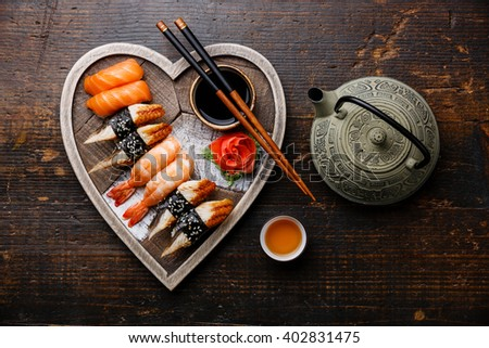 Sushi Set nigiri and tea served on Heart shape wooden tray on dark wooden background - stock photo
