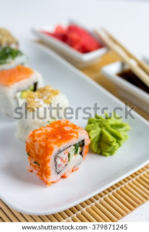 Sushi set on white wooden background with wasabi, ginger and soy sauce