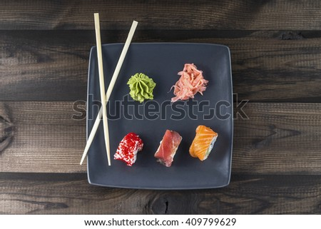 Sushi set. Red Spider Roll, Orange Spider Roll and Tobico Roll with pickled ginger and wasabi served on grey plate with sushi sticks on wooden table. Top view. - stock photo