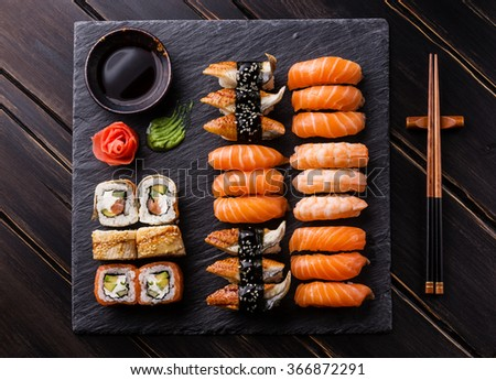 Sushi Set sashimi and sushi rolls on black stone slate - stock photo
