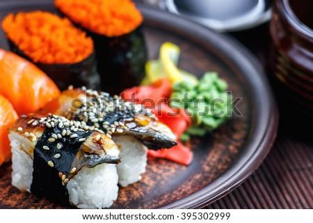 Sushi Set sashimi and sushi rolls served on dark plate. Image of Japanese food on dark background. - stock photo