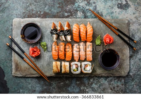 Sushi Set sashimi and sushi rolls served on stone slate - stock photo