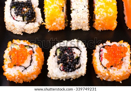 Sushi set served on a plate on black background, close up - stock photo