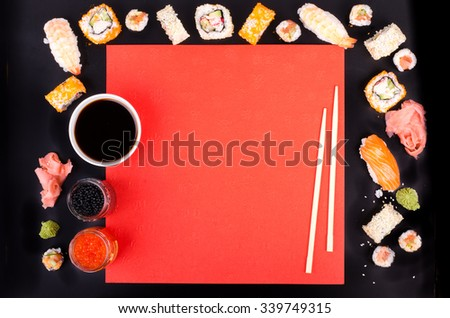 Sushi set, soy sauce, wasabi on black and red background - stock photo