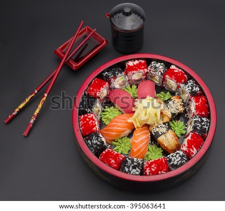 Sushi set with ginger wasabi and chopsticks and soy saue over stone background - stock photo