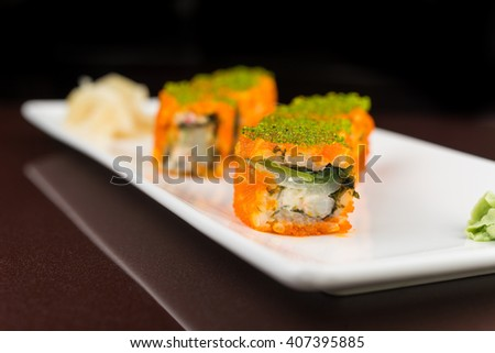 Sushi set with salmon in white dish on brawn background