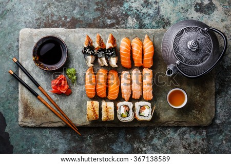 Sushi Set with tea served on gray stone slate on metal background - stock photo