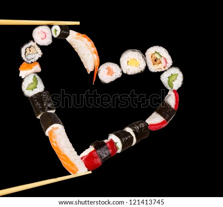 Sushi sticks holding pieces of sushi in heart shape, isolated on black background - stock photo