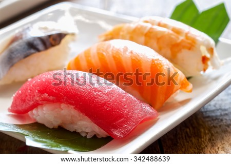 sushi with chopsticks.albacore,shrimp, salmon,tuna,and wasabi on the wood table - stock photo