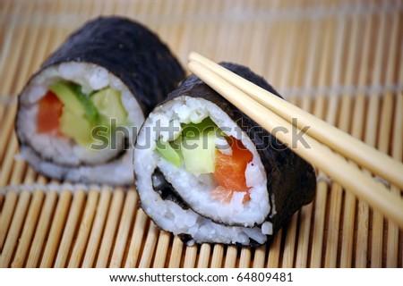 Sushi with chopsticks isolated on the straw background - stock photo