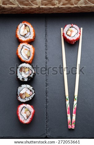 sushi with chopsticks on a dark background - stock photo