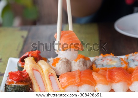 Sushi with chopsticks , selective focus point.