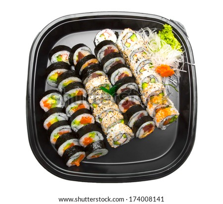 Sushi with maki rolls and garnish on a black plastic tray.