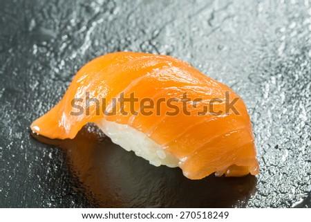 sushi with organic salmon on black background - stock photo