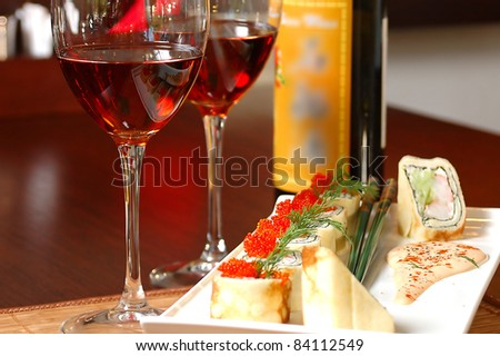 sushi with red wine on a table at restaurant - stock photo