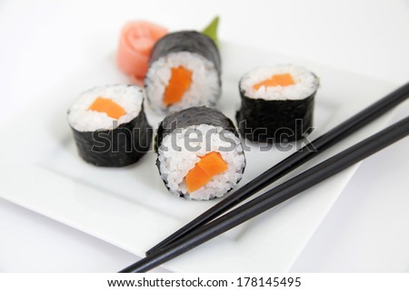 Sushi with rice and carrot on white plate