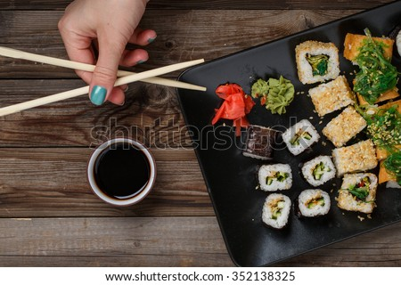 Sushi. Womans hand with chopsticks. Sushi set at black plate on wood table. - stock photo