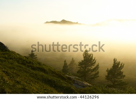 Susnset in the foggy mountains - stock photo