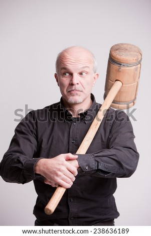 suspect man with a wooden big hammer pretends to be indifferent - stock photo
