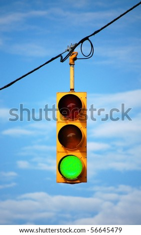 Suspended stoplight showing green, with sky background - stock photo