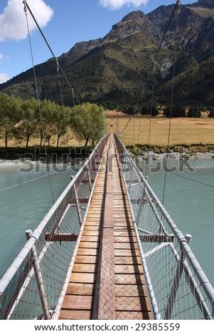 Suspended wire bridge - river crossing on a tourist trail in Mount Aspiring National Park, New Zealand - stock photo