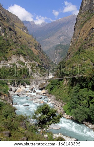 Suspension brdge and mountain river in Nepal  - stock photo