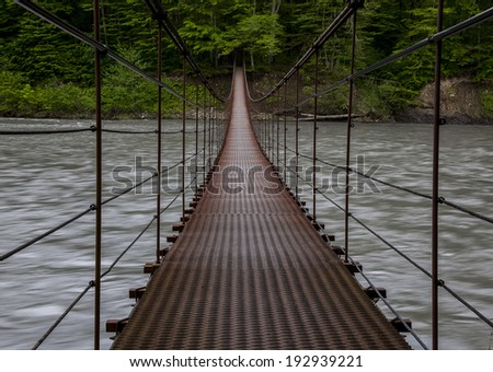 suspension bridge above the river rainforest