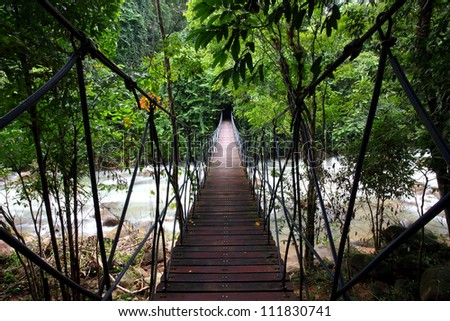 Suspension bridge across a stream in the jungle  at east, Thailand - stock photo