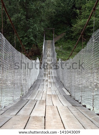 Suspension bridge across mountain river. Shallow depth of field. Focus in the the middle of the bridge.