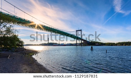 Suspension bridge at Gothenburg Connecting main land to Industrial area of Hisingen in west coast of Sweden. During summer sun sets next to power plant