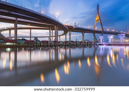 Suspension bridge connect to highway intersection river front after sunset - stock photo