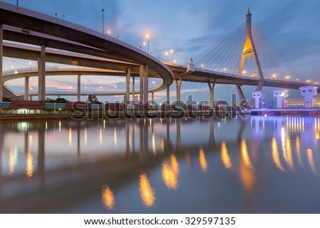 Suspension bridge curved riverside view during twilight - stock photo