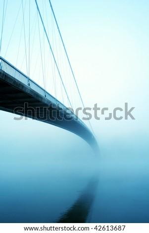 Suspension bridge in fog - stock photo